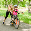 happy mother teaches his daughter to ride a bike