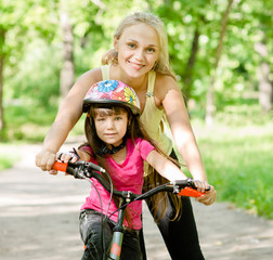 mother and daughter learning to ride a bicycle