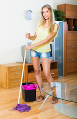 girl washing parquet floor with mop