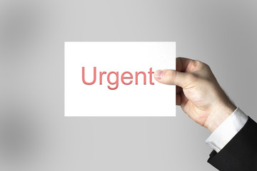 hand holding white card urgent