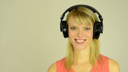 woman listens to music with headphones and smiles - studio