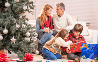 Happy family of four celebrating Chrismas near tree at home. Fam