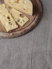 Cheese on the wood plank on the linen canvas