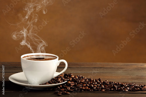 Foto op Canvas Koffie Black coffee in white cup with smoke and coffee beans on brown b