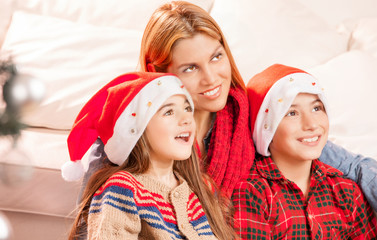 Mother with children at home for Christmas looking far with happ