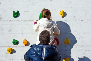 little girl climbing helped by his father