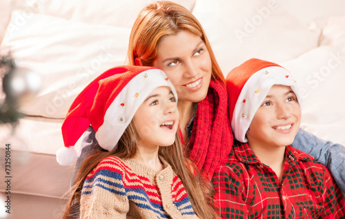 canvas print picture Mother with children at home for Christmas looking far with happ