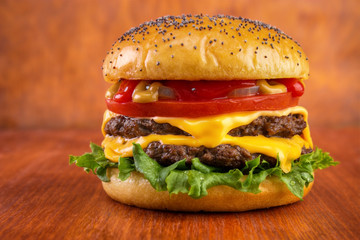 Double cheeseburger , red wooden background