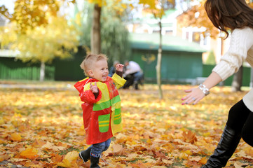 mother and the kid walk in autumn park