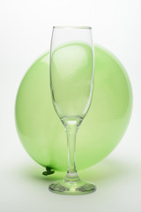 Copa de champán vacía y globo verde