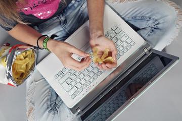 jeune fille mangeant chips sur ordinateur