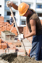 Bricklayer worker mixing concrete adhesive mixture with shovel