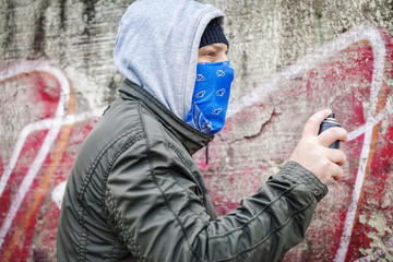 Man with color spray can near the old wall