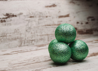 Green christmas balls in a stack over wooden background