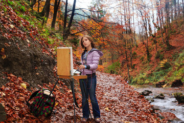 Young painter at work in the mountains