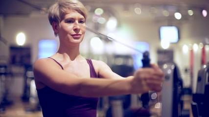 Junge Frau im Fitnessstudio trainiert Bauchmuskeln