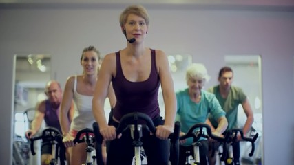 Senioren beim Spinning auf Fitness bike mit Instructor