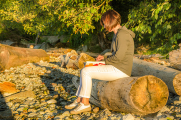 Young Woman Reading a Book on a Beach at Sunset