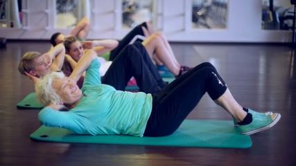 Junge und alte Leute beim Bauchmuskel Training
