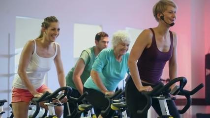 Senioren und Junge Spinning auf Fitness Fahrrad
