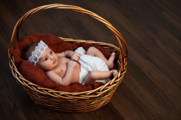newborn with a crown in  basket on  floor