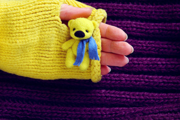 Toy yellow bear in hand