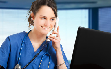 Young female nurse talking at the phone