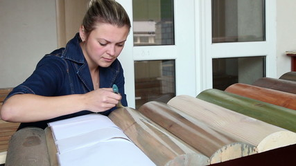 woman paints the wood with protective lacquer
