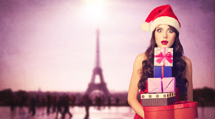 Beautiful brunette girl in christmas hat with gifts