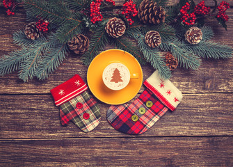 Hot cappuccino with christmas tree shape on a wooden table near