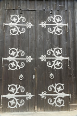 Barn doors with large decorative hinges.