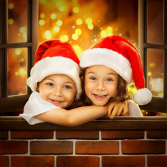 Happy kids in Santa hat  look out  window at Christmas time