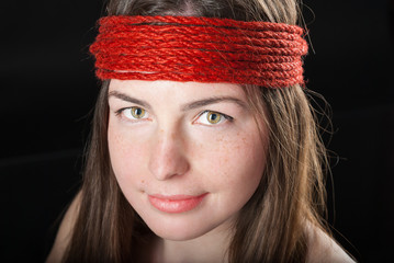 close-up portrait of beautiful woman with red rope