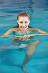 Frau schwimmt im Schwimmbad im Sommer