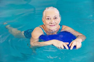 Alte Frau beim Schwimmen mit Schwimmbrett