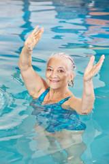 Seniorin hebt Arme beim Aquafitness
