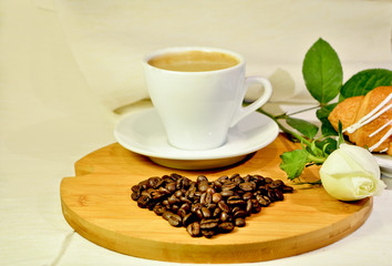 Cup of coffee with heart from the coffee beans and white rose