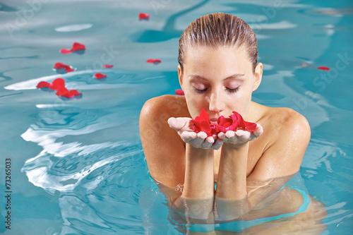 canvas print picture Frau im Wasser riecht an Blättern einer Rose
