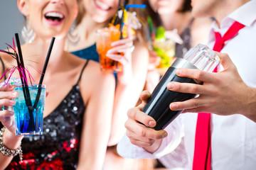 Freunde feiern mit Barkeeper in Cocktailbar
