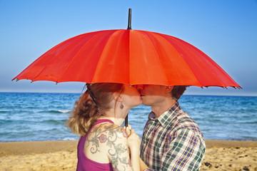 Enamorados besándose bajo sombrilla roja