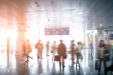 blurred passengers looking at airport schedule at sunny day