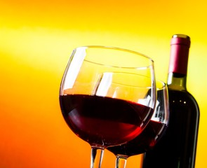 two red wine glasses near the bottle on golden lights background