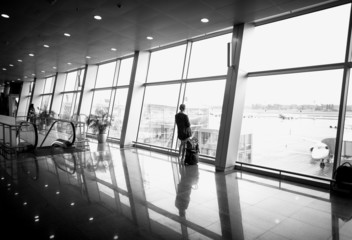 Monochrome  photo of woman standing in front of big window at ai