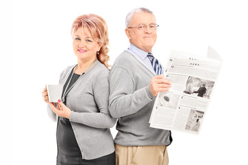 Mature couple with a newspaper and cup of coffee