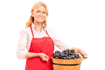 Mature lady holding a bucket full of grapes
