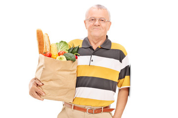 Senior gentleman posing with bag full of groceries