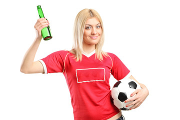 Young female fan holding a beer bottle and football