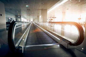 horizontal escalator at modern airport terminal at sun light