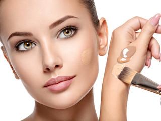 Makeup artist applying liquid tonal foundation  on the face