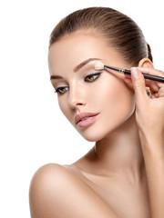 Beautiful woman applying eyeshadow use makeup brush